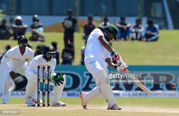 Bangladesh cricketer Tamim Iqbal plays a shot as Sri Lanka wicketkeeper Niroshan Dickwella looks on during the second day of the opening Test cricket...