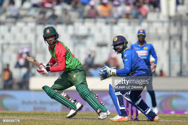 Bangladesh cricketer Tamim Iqbal plays a shot as the Sri Lanka wicketkeeper Niroshan Dickwella looks on during the third one day international...