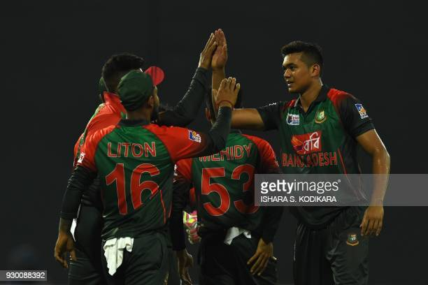 Bangladesh cricketer Taskin Ahmed celebrates with his teammates after he dismissed Sri Lankan cricketer Dinesh Chandimal during the third Twenty20...