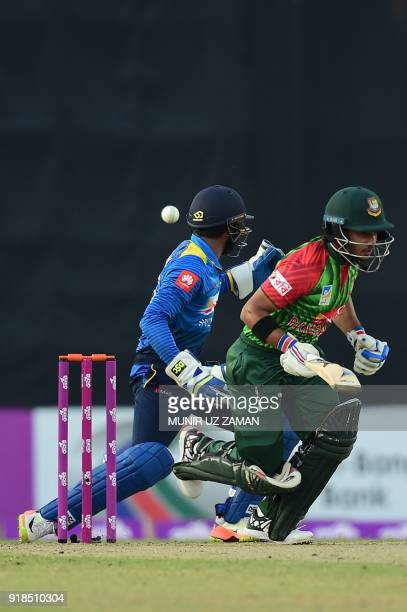 Bangladesh cricketer Zakir Hasan bats as Sri Lanka wicketkeeper Niroshan Dickwella looks on during the first Twenty20 cricket match between...