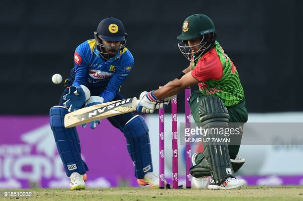 Bangladesh cricketer Zakir Hasan bats as the Sri Lanka wicketkeeper Niroshan Dickwella looks on during the first Twenty20 cricket match between...