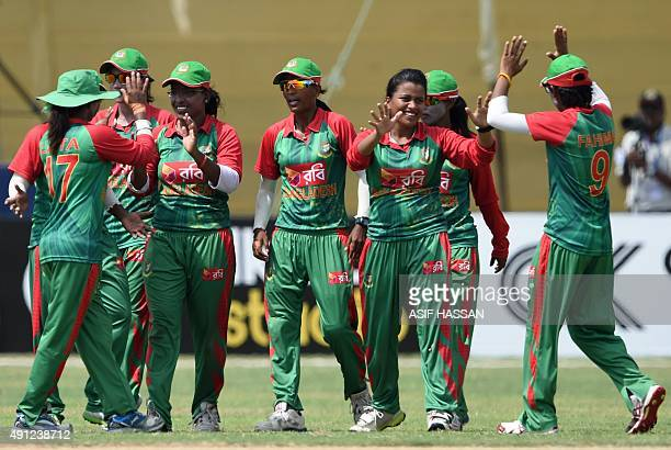 Bangladesh cricketers celebrate after dismissal of unseen Pakistani cricketer Sana Mir during the first one day international cricket match between...