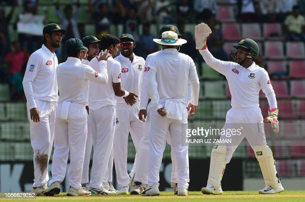 Bangladesh cricketers congratulate teammate Taijul Islam after the dismissal of Zimbabwe cricketer Brian Chari during the first day of the first Test...