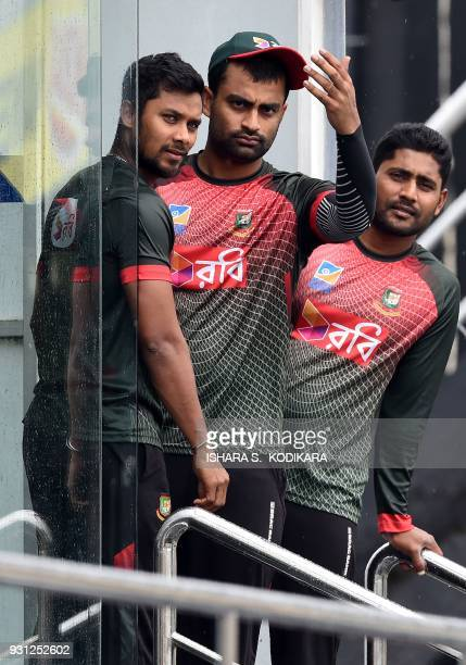 Bangladesh cricketers Imrul Kayes Sabbir Rahman and Tamim Iqbal look on from the dressing room after rain delayed a training session at the R...