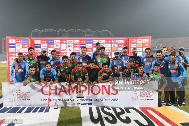 Bangladesh cricketers pose with the series trophy following the presentation ceremony after their victory in the third one day international cricket...