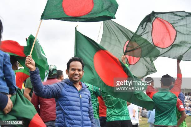Bangladesh fans wave their national flags during the second oneday international cricket match between New Zealand and Bangladesh at Hagley Oval in...