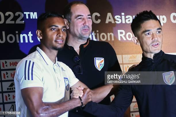 Bangladesh' football captain Jamal Bhuyan shakes hands with Indian captain Sunil Chhetri as India's coach Igor Stimac looks on during a press...