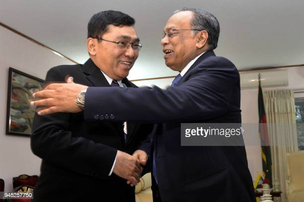 Bangladesh Foreign Minister Abul Hasan Mahmud Ali shakes hands with Myanmar Social Welfare Minister Win Myat Aye during their meeting in Dhaka on...