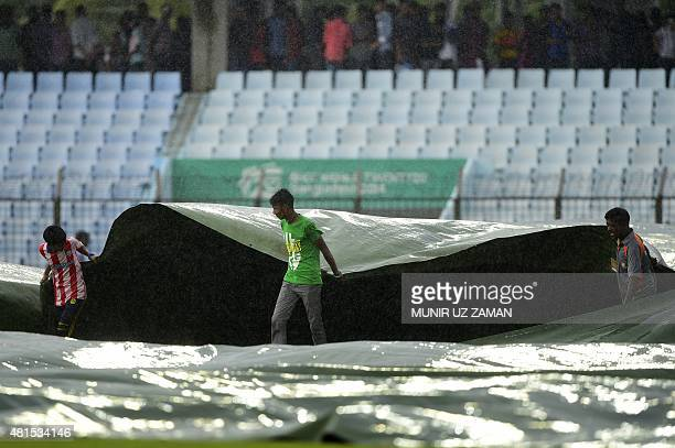 Bangladesh ground staff cover the field as rain falls during the second day of the first cricket Test match between Bangladesh and South Africa at...