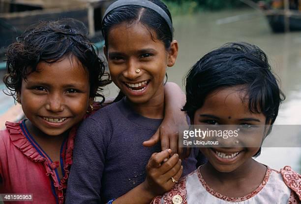 Bangladesh Khulna Char Kukuri Mukuri Head and shoulders group portrait of three smiling young girls