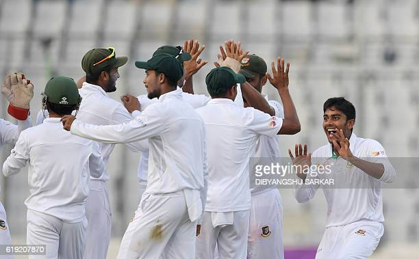 Bangladesh Mehedi Hasan with teammates celebrates the wicket of England's captain Alastair Cook during the third day of the second Test match between...