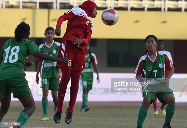 Bangladesh midfielder Maynu Marma and forward Mossamat Munmun Akter look on as Maldives forward Mariyam Rifa heads the ball during the final match of...