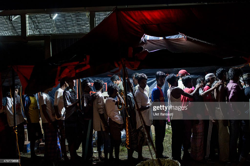 Bangladesh migrants stand line up to get medical treatment at a temporary shelter on May 17, 2015 in Kuala Langsa, Aceh province, Indonesia. Hundreds of Myanmar's Rohingya refugees arrived in Indonesia on May 15, many requiring medical attention. Thousands more are believed to still be stranded at sea reportedly with no country in the region willing to take them in. Myanmar's Rohingya Muslim community have long been persecuted and marginalized by Myanmar's mostly Buddhist population.