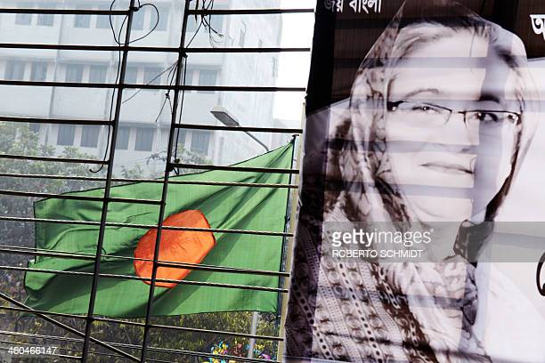 A Bangladesh national flag flutters beside an image of Prime Minister Sheikh Hasina affixed at a government community centre in Dhaka on January 4...