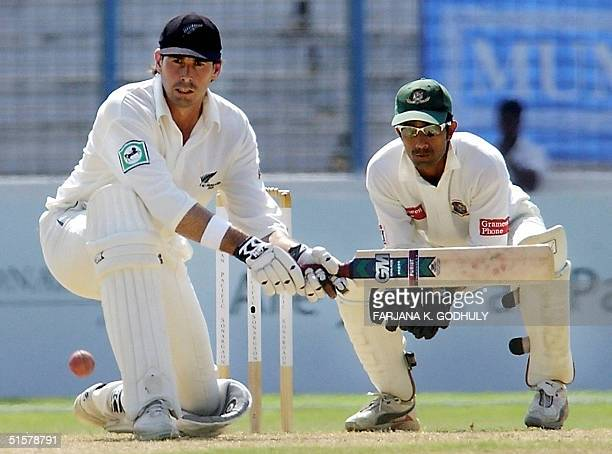 New Zealand captain Stephen Fleming hits a ball as Bangladeshi wicket keeper Khaled Mashud looks on during the second day of the second Test match...