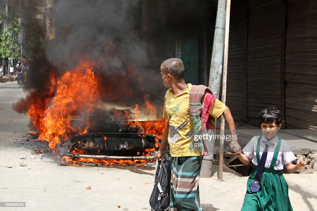 Bangladesh pedestrians walk past a burning vehicle set afire by activists of the Jamaat-e-Islami who burst into violent protests in Chittagong on September 17, 2013, after a verdict was delivered against Abdul Quader Molla, the fourth-highest leader of the Jamaat-e-Islami party. Bangladesh's top court sentenced to death a senior Islamist opposition official for murder during the 1971 liberation war against Pakistan. Abdul Quader Molla is the first politician to be found guilty by the country's Supreme Court after it rejected an appeal to acquit him of all charges.