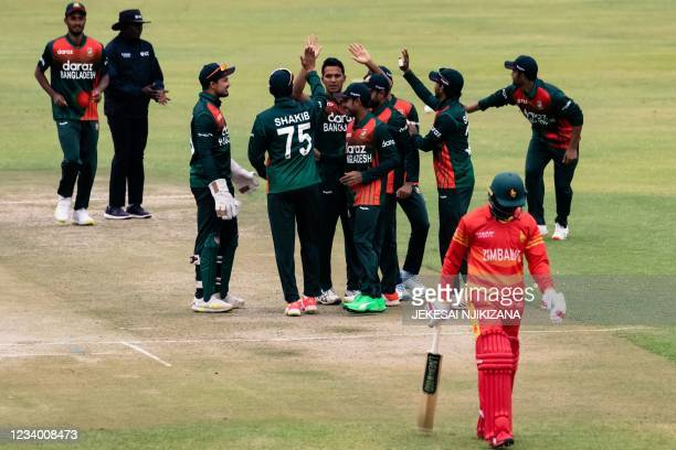 Bangladesh players celebrate as Zimbabwe's Tadiwanashe Marumani walks off the field after loosing his wicket during the first One-Day International...