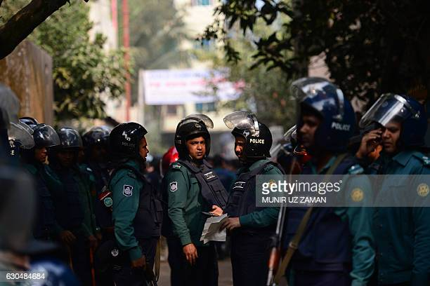Bangladesh police officials stand alert at the scene of an operation to storm an alleged militant hideout in Dhaka on December 24 as a team from the...