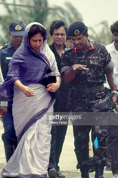 Bangladesh prime minister Khaleda Zia is guided by an army officer during a visit to an area of her country devastated by a cyclone in 1991
