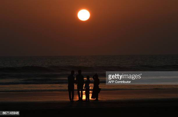 TOPSHOT Bangladesh residents look towards a sunset in the beach of Teknaf on October 27 2017 / AFP PHOTO / Tauseef MUSTAFA