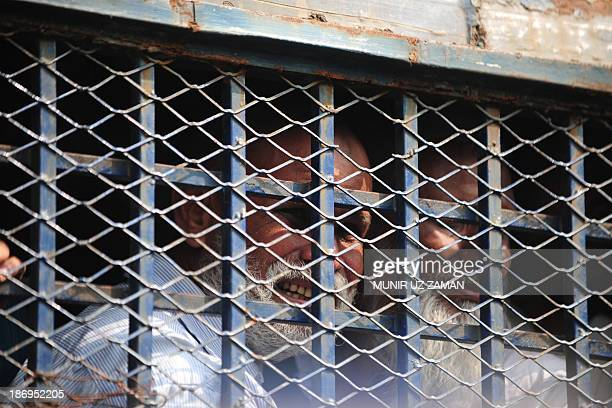 Bangladesh Rifles soldiers look through a prison van as they leave the court premises following their verdict in Dhaka on November 5 2013 A...