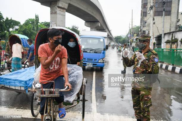 Bangladesh soldier wearing mask and gloves stands on guard along the road as part of a measure to stem the spread of the coronavirus pandemic....