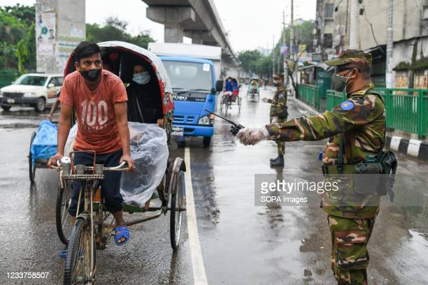 Bangladesh soldiers wearing masks and gloves stand on guard along the road as part of a measure to stem the spread of the coronavirus pandemic....