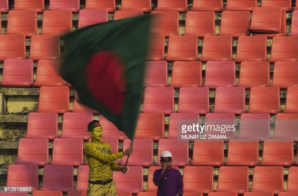 A Bangladesh spectator weaves national flag during the first day of the first cricket Test between Bangladesh and Sri Lanka at Zahur Ahmed Chowdhury...