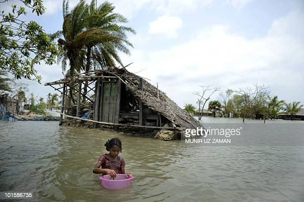 BangladeshcyclonemigrationwarmingFEATURE by Cat Barton A Bangladeshi child washes fish in front of a partially flooded home during tidal movements in...