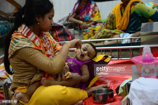 Bangladeshi a mother feeding Saline her children who is suffering from diarrhea lie at The International Centre for Diarrhea Disease Research...