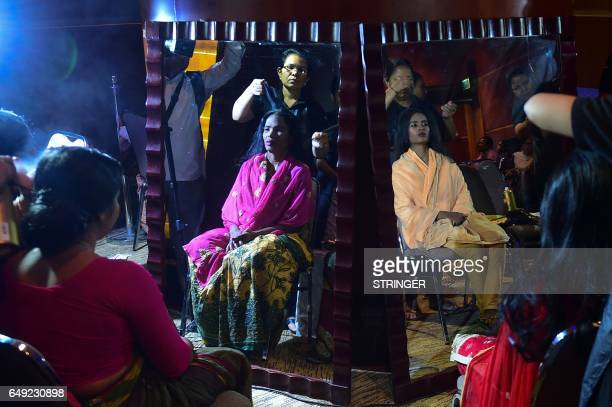 Bangladeshi acid attack survivors are reflected in mirrors as they have their hair done backstage prior to the fashion show 'Beauty Redefined' by...