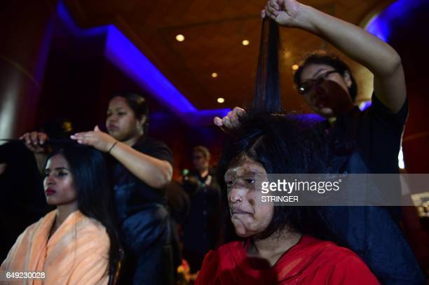 Bangladeshi acid attack survivors have their hair done backstage prior to the fashion show 'Beauty Redefined' by designer Bibi Russell featuring acid...