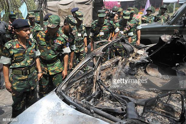 A Bangladeshi Army investigation team inspects the wreckage of a burntout car set fire during the February 25 mutiny in the compounds of the...