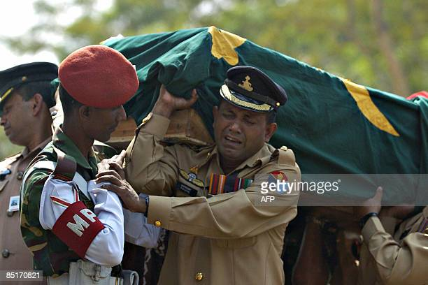 A Bangladeshi Army officer breaks down in tears as he carries the coffin of a comrade killed during a mutiny during a funeral ceremony in Dhaka on...