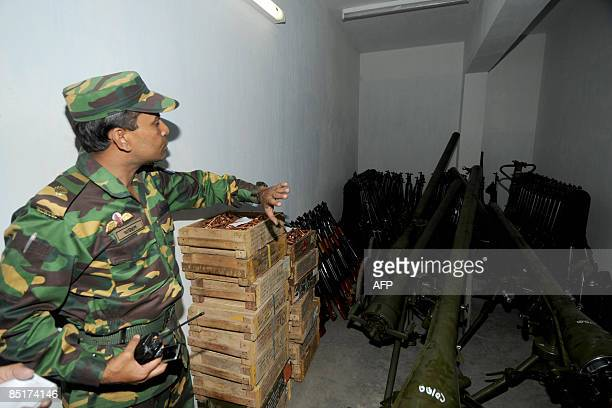 A Bangladeshi army officer shows the arms used by the rebels during the recent mutiny at the Bangaldesh Rifles heaquarters in Dhaka on March 2 2009...