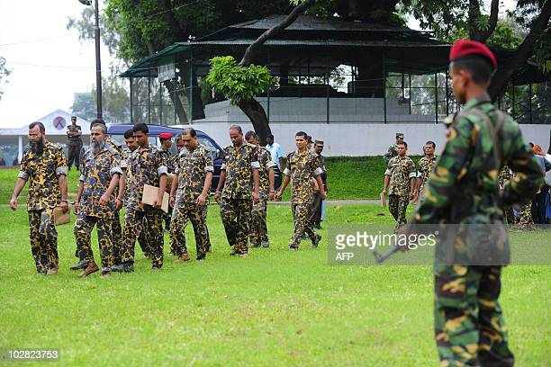 A Bangladeshi army soldier stands guard as handcuffed Bangladesh Rifles headquarter battalion soldiers walk to a special mutiny court at BDR...