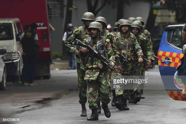 TOPSHOT Bangladeshi army soldiers patrol a street during a rescue operation as gunmen take position in a restaurant in the Dhakas highsecurity...