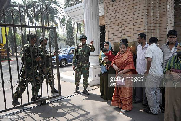 Bangladeshi Army troops close the main entrance to the Bangladesh Rifles headquarters as worried relatives of Bangladesh Rifles personnel wait...