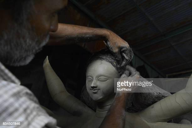 A Bangladeshi artist prepares a clay idol of Hindu deity Durga at a workshop ahead of Durga puja festival in Dhaka Bangladesh on August 18 2017 The...