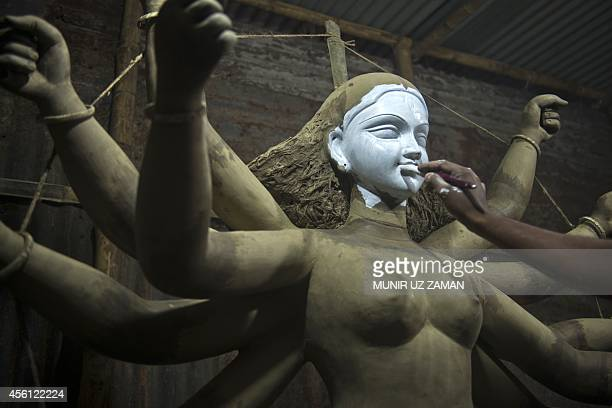 A Bangladeshi artist works on a clay idol of the Hindu Goddess Durga in preparation for the upcoming Hindu festival Durga Puja in Old Dhaka on...