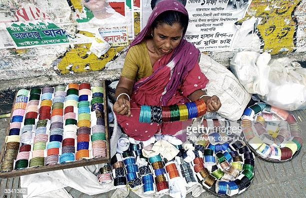 Bangladeshi bangle vendor arranges her wares at her pavement stall on the eve of Bengali New Year in Dhaka 12 April 2004 Across the country the first...