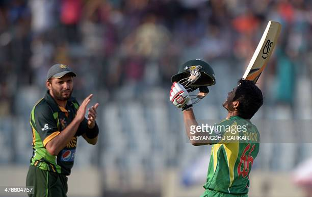 Bangladeshi batsman Anamul Haque celebrates after scoring a century as Pakistani fielder Shahid Afridi applauds during the eighth match of the Asia...