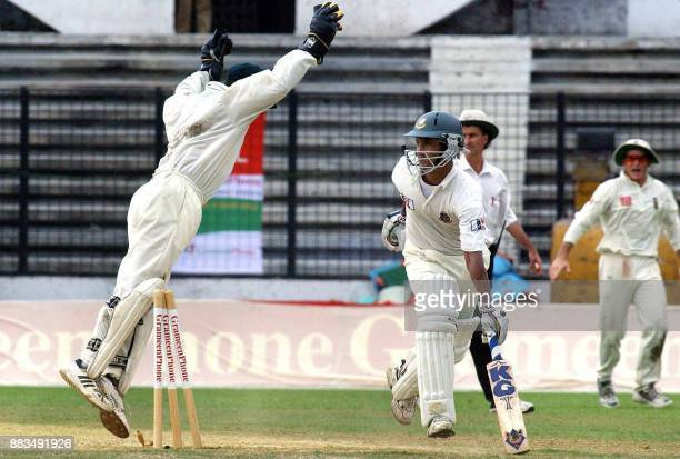 Bangladeshi batsman Mehrab Hossain unsuccessfully tries to save his wicket as South African wicketkeeper Mark Boucher breaks it during the third day...