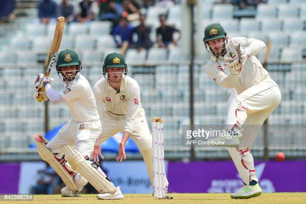 Bangladeshi batsman Mominul Haque plays a shot in front of Australian wicketkeeper Matthew Wade during the first day of the second cricket Test match...