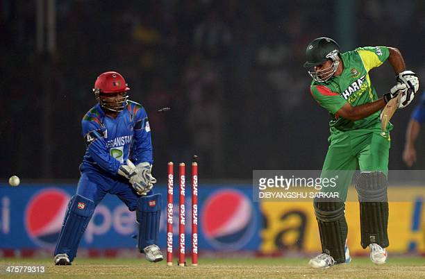 Bangladeshi batsman Ziaur Rahman is watched by Afghan wicket keeper Mohammad Shahzad as he is clean bowled during the fifth match of the Asia Cup...