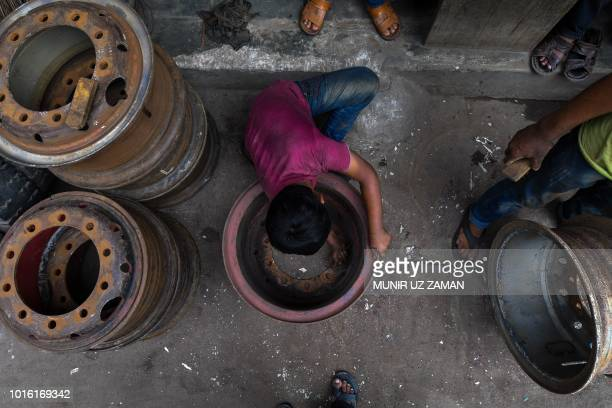 A Bangladeshi boy cleans rust from a used rim in Dhaka on August 13 2018
