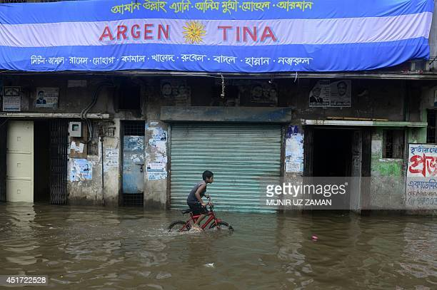 A Bangladeshi boy cycles through flood waters in old Dhaka on July 5 2014 Seasonal monsoon rains brought Dhaka to a standstill with vehicles scarce...