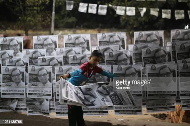 A Bangladeshi boy decorates posters of Bangladesh Awami Leagues MP candidate as participate in general election campaign in Dhaka Bangladesh on...