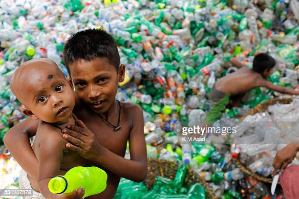 Bangladeshi brothers while their mother and other labourers sift through empty bottles at a plastic bottle recycling centre in Dhaka Bangladesh April...