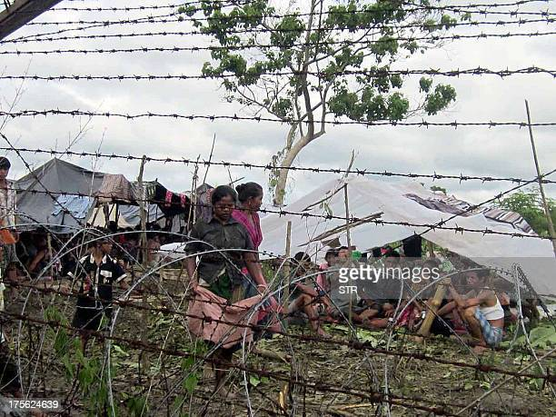 Bangladeshi Chakma women walk alongside barbed wire fencing as others sit under makeshift shelters at the Indo Bangladesh fencing area at Karbook 135...